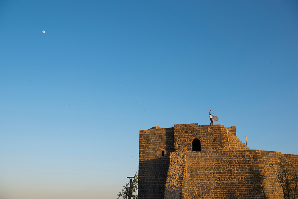 Early on a summer evening, a man prepares to fly a kite from atop the old city walls in Diyarbakir, Turkey. The famous walls, with numerous towers, gates, buttresses, and 63 inscriptions, and built of black basalt, stretch 5.8 kilometers around the old city. (June 5, 2017)