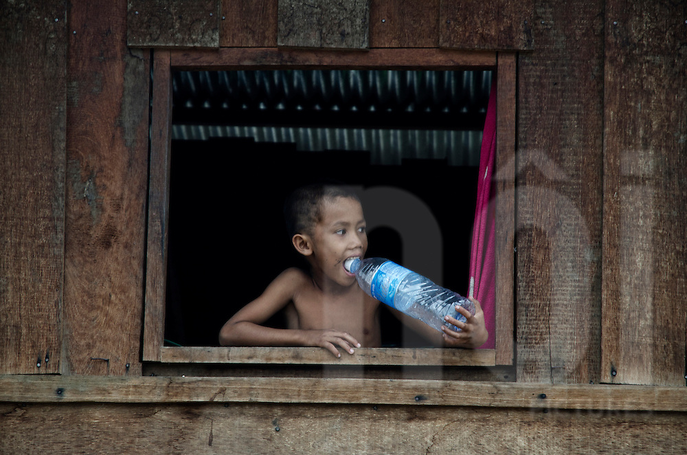 Portraiture of a Laos kid standing in an open window frame and eating top cap of a water bottle. Sekong Province, Laos, Asia