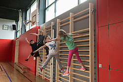 Four children exercising on wall bars in sports hall, Munich, Bavaria, Germany