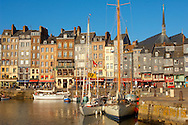 harbour scene with yaughts and harbour restaurants. Honfleur, Normandy, France. . Honfleur is especially known for its old port, characterised by its houses with slate-covered frontages, painted many times by artists, including in particular Gustave Courbet, Eugène Boudin, Claude Monet and Johan Jongkind, forming the école de Honfleur (Honfleur school) which contributed to the appearance of the Impressionist movement. .<br /> <br /> Visit our FRANCE HISTORIC PLACES PHOTO COLLECTIONS for more photos to download or buy as wall art prints https://funkystock.photoshelter.com/gallery-collection/Pictures-Images-of-France-Photos-of-French-Historic-Landmark-Sites/C0000pDRcOaIqj8E