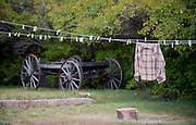A rural America scene  with flannel shirt hangs out to dry with an old wooden wagon in the background. Missoula Photographer, Missoula Photographers, Montana Pictures, Montana Photos, Photos of Montana