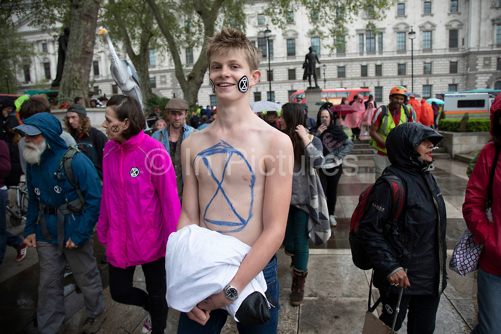 Climate change activist from the Extinction Rebellion group with an ER sticker on his face and the logo painted on his chest at Parliament Square in protest that the government is not doing enough to avoid catastrophic climate change and to demand the government take radical action to save the planet, on 24th April 2019 in London, England, United Kingdom. Extinction Rebellion is a climate change group started in 2018 and has gained a huge following of people committed to peaceful protests.