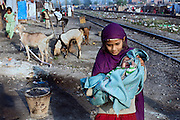 In the early morning, a young girl is carrying her crying sibling towards their home by the railway tracks in New Arif Nagar, one of the water-affected colonies standing next to the abandoned Union Carbide (now DOW Chemical) industrial complex, site of the infamous 1984 gas tragedy in Bhopal, Madhya Pradesh, central India. The poisonous cloud that enveloped Bhopal left everlasting consequences that today continue to consume people's lives.