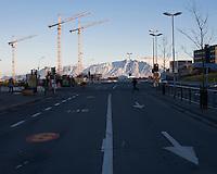 Lækjargata in Reykjavík City center. Three Building Cranes seem to watch a man running across the street. Lækjargata til Norðurs. Byggingarkranar fylgjast með manni hlaupa yfir götuna.