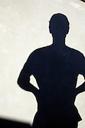 shadow of person standing with hands resting in his side