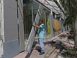 The Frieze Ice Cream Factory employee Martin Zelaya takes down storm shutters before opening for business in the Hurricane Irma aftermath on Tuesday, September 12, 2017, in Miami Beach. Photo by David Santiago/El Nuevo Herald/TNS/ABACAPRESS.COM