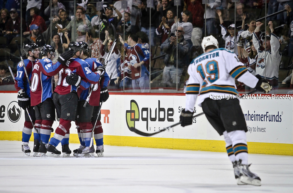SHOT 4/4/10 7:22:24 PM - Colorado Avalanche players celebrate a goal as the San Jose Sharks' Joe Thornton (#19) skates through the scene during the second period of their NHL regular season game at the Pepsi Center in Denver, Co. The Avalanche won the game 5-4 in overtime ending a four game losing streak and helping themselves in the race for the final playoff spot in the Western Conference. (Photo by Marc Piscotty / © 2010)