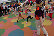 Children practice winning a sprint final on the grid-like patterned floor in the Olympic Park during the London 2012 Olympics. The kids race under a pretend track tape held by two volunteer Games Makers who offer the everyone winners' chocolate gold medals. This land was transformed to become a 2.5 Sq Km sporting complex, once industrial businesses and now the venue of eight venues including the main arena, Aquatics Centre and Velodrome plus the athletes' Olympic Village. After the Olympics, the park is to be known as Queen Elizabeth Olympic Park.