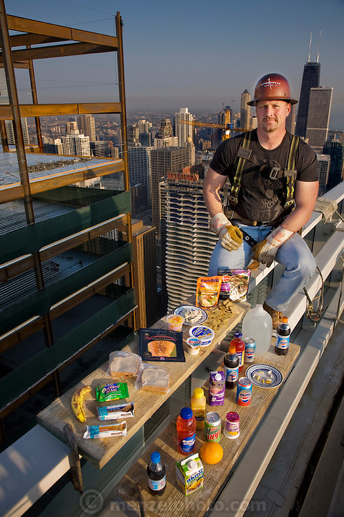 Overlooking his fiftieth floor worksite, ironworker Jeff Devine perches on the roof of a high-rise with his typical day's worth of food in Chicago.  (From the book What I Eat: Around the World in 80 Diets.) The caloric value of his typical day's worth of food on a day in the month of September was 6,600 kcals. He is 39 years of age; 6 feet, 1 inch tall; and 235 pounds. He carries a cooler of ready-to-eat food from home rather than eat at fastfood restaurants and vending trucks. MODEL RELEASED.