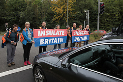 Godstone, UK. 13th September, 2021. Insulate Britain climate activists block a slip road from the M25, causing a long tailback on the motorway, as part of a new campaign intended to push the UK government to make significant legislative change to start lowering emissions. The activists, who wrote to Prime Minister Boris Johnson on 13th August, are demanding that the government immediately promises both to fully fund and ensure the insulation of all social housing in Britain by 2025 and to produce within four months a legally binding national plan to fully fund and ensure the full low-energy and low-carbon whole-house retrofit, with no externalised costs, of all homes in Britain by 2030 as part of a just transition to full decarbonisation of all parts of society and the economy.