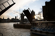Bridge at St Katherine Docks rises to let a boat onto the River Thames. London, UK.