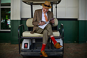 """30174108A LOUISVILLE, KY. - MAY 1, 2015: Donald Tatum, 87, of Louisville, Ky., looks through his Oaks program during the 141st running of the Kentucky Oaks at Churchill Downs. Tatum has been coming to Churchill Downs since 1941 where he use to earn cash picking up bottles. """"I like the horses,"""" Tatum said. """"It's just a fun atmosphere.""""<br /> <br /> William DeShazer for The New York Times"""