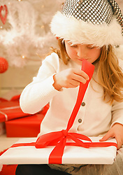 Close up of a girl in a furry hat unwrapping a Christmas gift