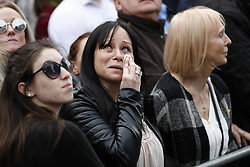 © Licensed to London News Pictures. 10/04/2017. London, UK. An emotional member of the public watches as The funeral cortege carrying the coffin of policeman Keith Palmer arrives at at Southwark Cathedral in London ahead of his funeral. PC Palmer was murdered just inside the gate by Westminster attacker Khalid Masood - an attack in which he also killed four people on Westminster Bridge.  Photo credit: Tolga Akmen/LNP