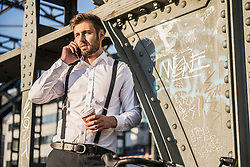 Businessman talking on mobile phone and drinking coffee, Munich, Bavaria, Germany