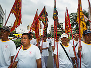 12 OCTOBER 2015 - BANGKOK, THAILAND:  Devotees march through Chinatown on the first day of the Vegetarian Festival in Bangkok's Chinatown. The Vegetarian Festival is celebrated throughout Thailand. It is the Thai version of the The Nine Emperor Gods Festival, a nine-day Taoist celebration beginning on the eve of 9th lunar month of the Chinese calendar. During a period of nine days, those who are participating in the festival dress all in white and abstain from eating meat, poultry, seafood, and dairy products. Vendors and proprietors of restaurants indicate that vegetarian food is for sale by putting a yellow flag out with Thai characters for meatless written on it in red.      PHOTO BY JACK KURTZ