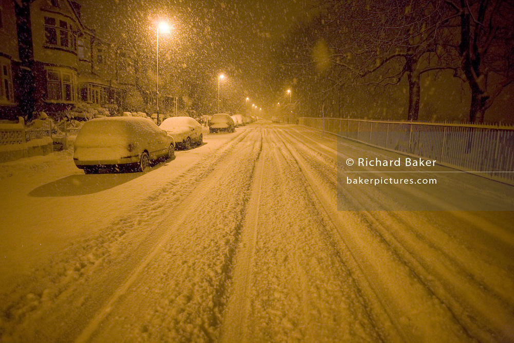 Snow showers are falling in a deserted South London street in Herne Hill, London SE24. Snowflakes are falling in large amounts settling on this road and tyre tracks from vehicles have been left in the snow though many parked cars are becoming covered in the snow fall as they sit at the kerbside. Snowflakes are falling in their thousands, settling on this part of London's inner-city - an unusual event - and the  heaviest precipitation for 18 years. It is early morning and still dark and street lights are making the landscape orange before the blue of dawn changes the colour and the atmosphere.