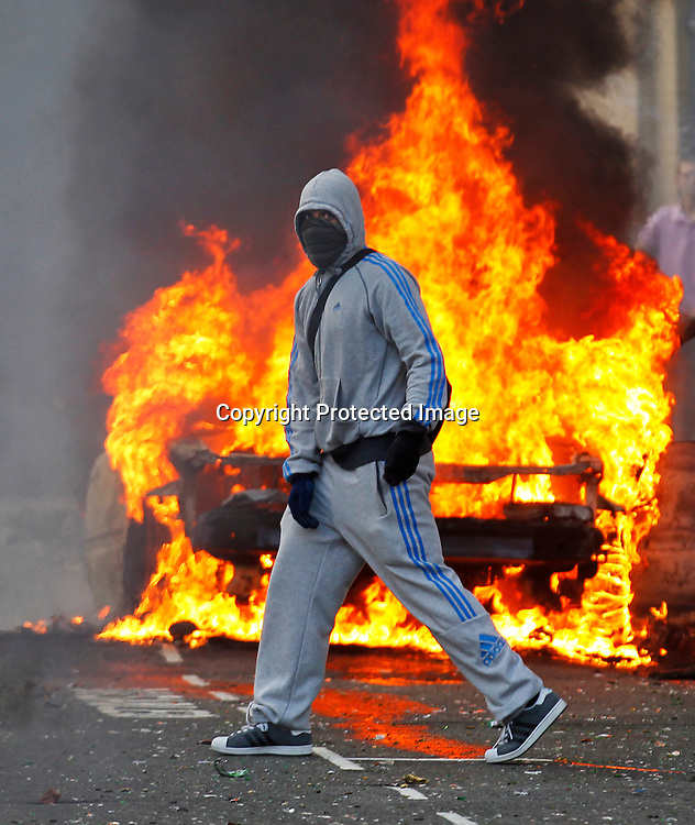 A masked rioter is seen in front of a burning car in Hackney, North London, Britain, 08 August 2011, during the third day of violence in London in which police have clashed with rioters in Hackney and vehicles have been set on fire in Peckham and Lewisham. Four days of riots were sparked after the police shot  a local 29-year-old Mark Duggan in Tottenham, on 04 August 2011. Hundreds were arrested and scores of police officers injured.According to reports up to 15,000 people may have taken part in the riots, most of them under 24.  EPA/KERIM OKTEN