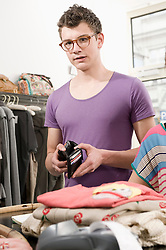 Portrait of young man holding wallet at cash counter