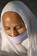 Portrait of a Jainist nun. Jainism is an ancient religion of India that prescribes a path of non-violence towards all living beings. The white cloth over their mouths is called Muhapatti to prevent saliva coming into contact with religous texts, and accidental inhaling of small insects. Bikaner, Rajasthan, India