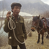 A Tibetan villager stands by his horse beside the Tsangpo River (Brahmaputra) in the Himalaya of remote southeastern Tibet, China.