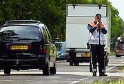Nederland, Oploo, 20-6-2005..Snelheidscontrole, snelheidskontrole door de politie. verkeerscontrole, overschrijding maximum snelheid, radardetector, radardetektor in personenauto's, verkeerspolitie, bekeuring, boete voor te hard, te snel rijden, provinciale weg, tweebaansweg. Rijgedrag, verkeersgedrag..Foto: Flip Franssen/Hollandse Hoogte