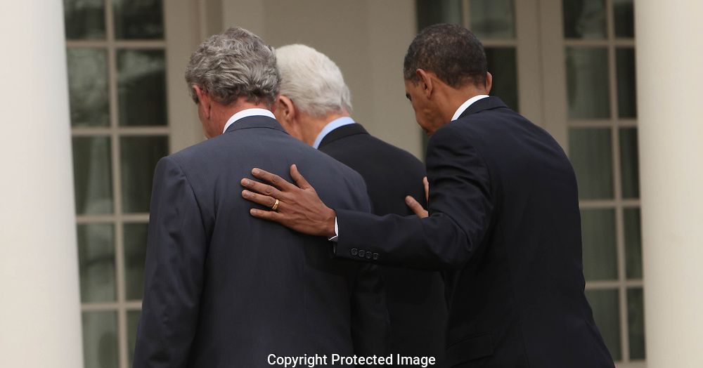 President Barack Obama and former presidents William Clinton and George W. Bush make an announcement about aid for Haiti in the Rose Garden of the White House.  Photograph by Dennis Brack