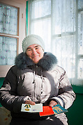 A retired BAM (Baikal-Amur Mainline) volunteer shows her paperwork from her time working on the railway in Baikalskoe Village on Lake Baikal. Siberia, Russia