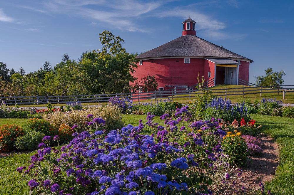 Round red barn of Shelburne Museum, with summer flower garden foreground, Shelburne, VT