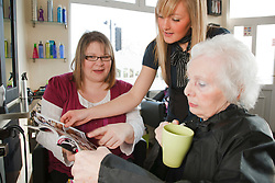 Carer with old lady at hairdresser's choosing hair style.