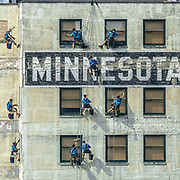 Ballet with soap and rags at the end of ropes on the side of the Minnesota Building.