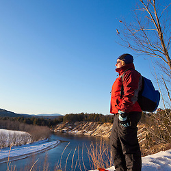A woman snowshoeing on a bluff overlooking the Merrimack River in Canterbury, New Hampshire.