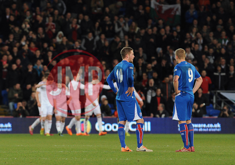 Gylfi Thor Sigurdsson (Tottenham Hotspur) of Iceland and Kolbeinn Sigthorsson (Ajax) of Iceland cut dejected figures as Wales celebrate their second goal scored by Sam Vokes - Photo mandatory by-line: Dougie Allward/JMP - Tel: Mobile: 07966 386802 03/03/2014 -