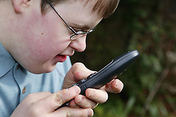 Teenage Downs Syndrome boy using a large button portable telephone,