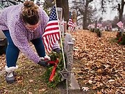 14 DECEMBER 2019 - DES MOINES, IOWA: STEFANIE HARPER, from Johnston, IA, places a Christmas wreath on a veteran's grave. Volunteers working with Wreaths Across America placed Christmas wreaths on the headstones of more than 600 US military veterans in Woodland Cemetery in Des Moines. The cemetery, one of the first in Des Moines, has the graves of veterans going back to the War of 1812.           PHOTO BY JACK KURTZ