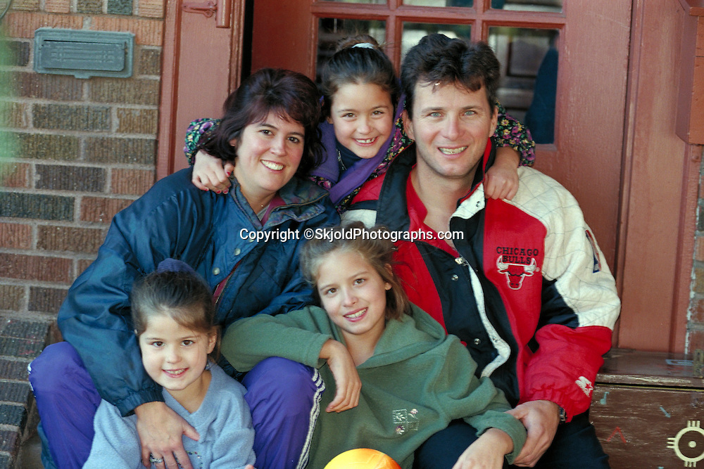 Happy family ages 35 and 9 through 5 sitting on front steps of house.  St Paul  Minnesota USA