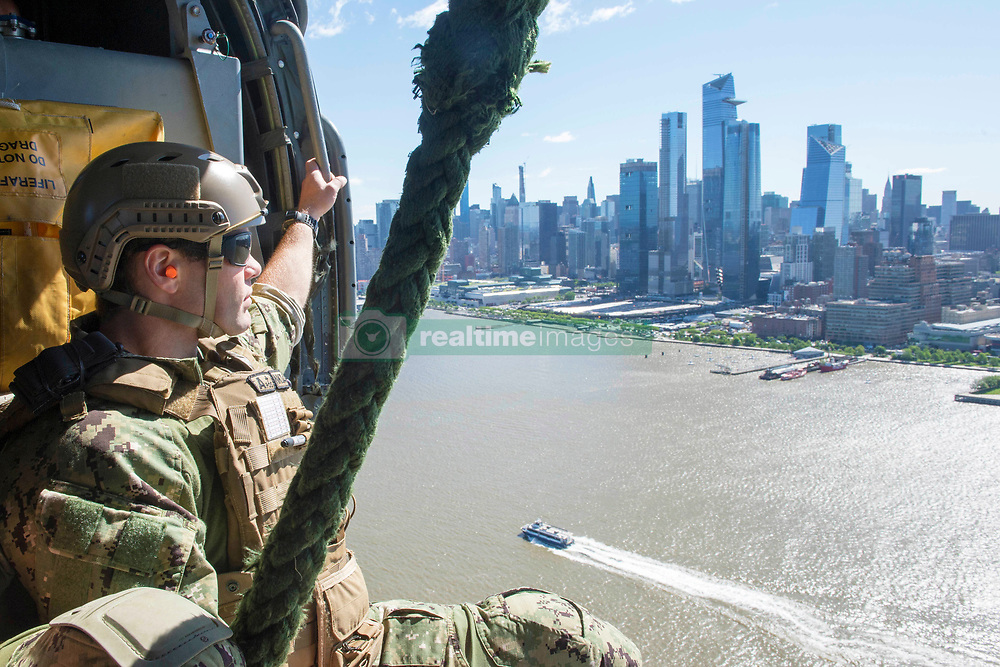 """May 21, 2019 - New York, New York, U.S. - An explosive ordnance disposal (EOD) technician assigned to EOD Mobile Unit (EODMU) 6 flies along the New York city skyline in an MH-60S Sea Hawk assigned to the """"Tridents"""" of Helicopter Sea Combat Squadron (HSC) 9 during Fleet Week New York. Fleet Week New York, now in its 31st year, is the city's time-honored celebration of the sea services. It is an unparalleled opportunity for the citizens of New York and the surrounding tri-state area to meet Sailors, Marines and Coast Guardsmen, as well as witness firsthand the latest capabilities of today's maritime services. (Credit Image: ? U.S. Navy/ZUMA Wire/ZUMAPRESS.com)"""