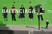 Shoppers and the temporary construction hoarding for Balenciaga, a retail space which is opening soon on Bond Street, on 27th April 2021, in London, England. Balenciaga is a fashion house founded in 1917 by Spanish designer Cristóbal Balenciaga in San Sebastián, Spain.