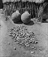 Karamajong village with fruit skins drying in the sun with traditional thatched raised storage huts and grain bins - Karamoja, Uganda 1980
