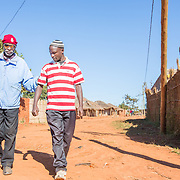 CAPTION: Mobility continues to be one of the biggest challenges that people with disabilities (PWDs) face. Living in Mozambique's Niassa Province, Casimiro Aduwa Caisse is a small business owner who lost his sight at the age of 18. Here, his son is seen guiding him along the road. Caisse struggled to find his feet after his impairment, which left him unable to continue with his work. The struggle endured until he found the Association of Blind and Partially Sighted People (ACAMO) in 2002. His involvement with this organisation gave him a new lease of life, and he devoted himself to this. Over the years, he has risen to become ACAMO's Second Provincial Delegate. LOCATION: Nzinje Village, Lichinga, Niassa Province, Mozambique. INDIVIDUAL(S) PHOTOGRAPHED: Casimiro Adua Caisse (left) and Boaventura Casimiro (right).