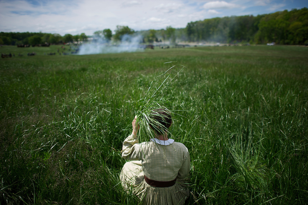 With a makeshift parasol of tall grasses, Brittney Mumma, 17, of the Civil War Civilians of Spotsylvania, observes the Chancellorsville 150th reenactment from a distance on May 4, 2013 in Chancellorsville, VA.