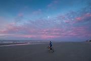 A bicyclist rides on the beach at Wild Dunes resort as dawn breaks June 13, 2017 in Isle of Palms, South Carolina. Isle of Palms is a sea island along the Atlantic coast near Charleston, South Carolina.