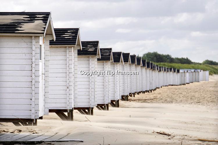 Nederland, Groede, 5-9-2019 Strand met strandhuisjes en helmgras tegen de duinen in de wind.. Foto: Flip Franssen