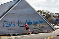 Brandy Wood Jessen praypaints a message on the top of a house that washed up on HWY 98 in Mexico Beach , Florida following Hurricane Michael