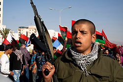 © licensed to London News Pictures. BENGHAZI. 15/04/2011.  An armed revolutionary guards a woman's march after Friday's prayer in Benghazi. Please see special instructions for usage rates. Photo credit should read ISMAIL NEGM/LNP