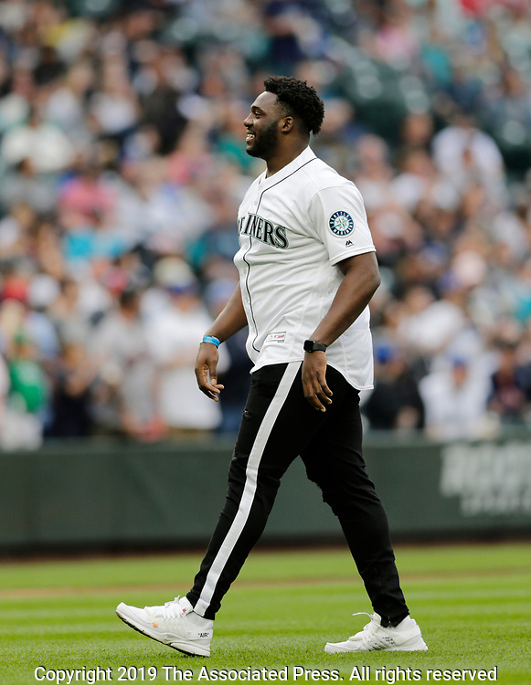 Seattle Seahawks first round draft pick L.J. Collier throws out the first pitch before a baseball game between the Seattle Mariners and the Minnesota Twins, Saturday, May 18, 2019, in Seattle. (AP Photo/John Froschauer)