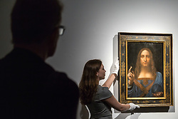 London, October 24 2017. A gallery assistant straightens Leonardo da Vinci's Salvator Mundi ('Saviour of the World'), estimated at $100 million at Christie's in London, which will be sold in the Post-War and Contemporary Art Evening Auction taking place on 15 November at Christie's New York. The painting is one of fewer than 20 known paintings by Leonardo, and the only one in private hands. © Paul Davey