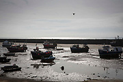 Fishing boats sit on the sand in a dry harbour due to the tide being out. Folkestone Harbour, Kent, United Kingdom.