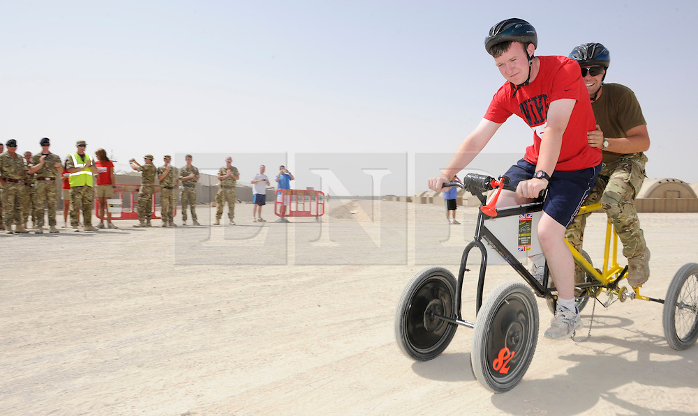 © Licensed to London News Pictures. 18/08/2011. Bastion, Afghanistan. Royal Air Force engineers who are normally busy keeping helicopters in the air take a break from the flight line to take part in a 'make your own' Kart race at Camp Bastion.  The race was organised to raise money for Kart Force, a UK based charity that modifies go karts so that they can be used by amputees and injured soldiers.  Photo credit : Sergeant Alison Baskerville/LNP