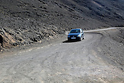 Car driving on unsurfaced road,  Jandia peninsula, Fuerteventura, Canary Islands, Spain